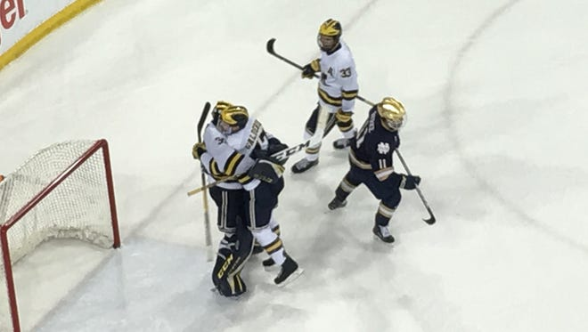 Tony Calderone jumps into the arms of goalie Hayden Lavigne at the conclusion of Michigan's 1-0 win over Notre Dame on Sunday.