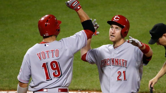 The Reds' Todd Frazier celebrates with teammate Joey Votto after hitting a solo home run Tuesday during the ninth inning in Pittsburgh.