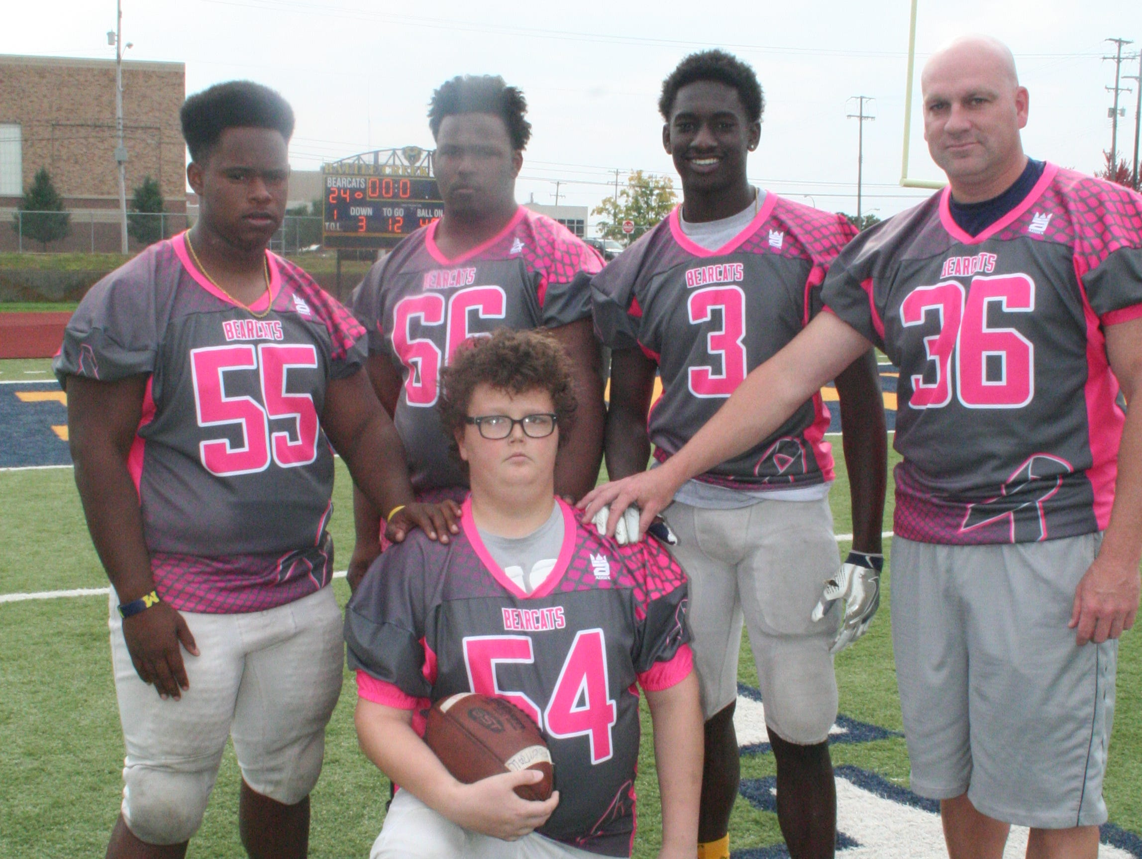 Battle Creek Central will host a Grey/Pink Game to raise money for freshman Michael Miller, front, who has brain cancer. He is joined by varsity players, from left, Wisdom Morris, Jaylen Walker, Austin McKinney and BCC Coach Lorin Granger.
