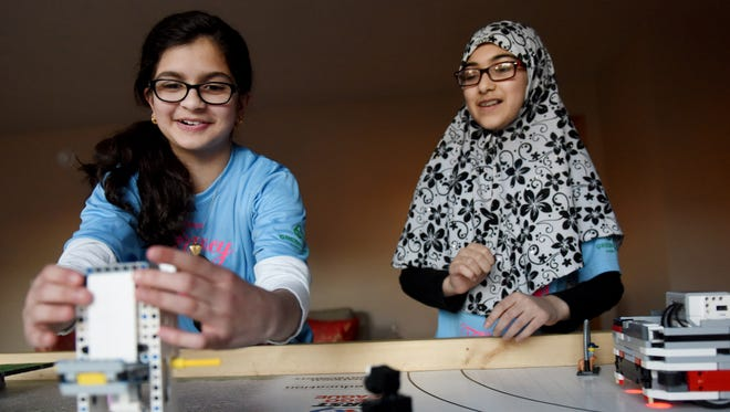Tuba Ali, 12, (left) and Halima Niazi, 12, with the 'Fancy Flamingos'  First Lego League team demonstrate how their programmed robots score points.