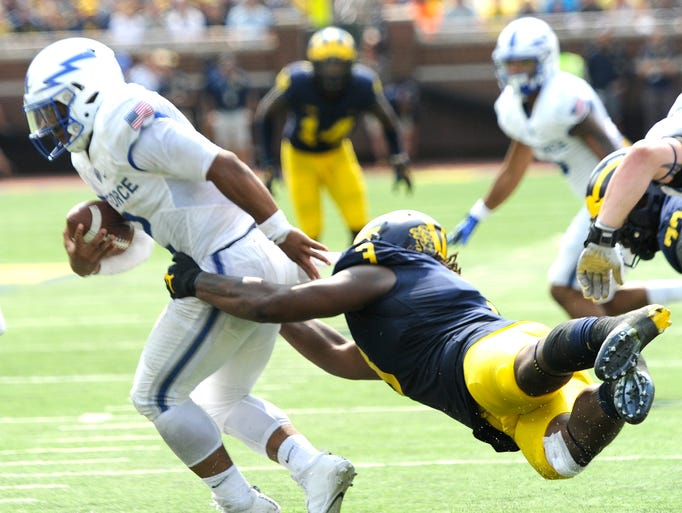 Michigan's Rashan Gary (3) holds on as he tackles Air