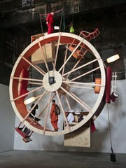 """The performance art """"In Orbit,"""" a 25-foot wheel made from wood, steel, and furniture, is home for artists Ward Shelley, top, and Alex Schweder, bottom, for 10 days at the Boiler gallery in Williamsburg, Brooklyn, Tuesday, March 4, 2014. They  share two living units arrayed over the hamster-wheel-like sculpture, with Shelly living on the outside and Schweder on the inside. The structure will remain on view through April 5, 2014."""