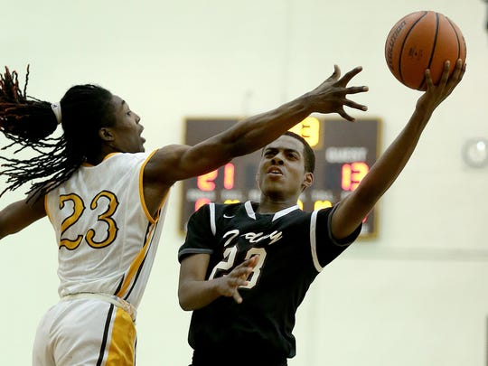Tindley's Tyler Young (23) lays up a shot around Howe in the Indianapolis City Boys Basketball Tournament, Jan 21, 2016.