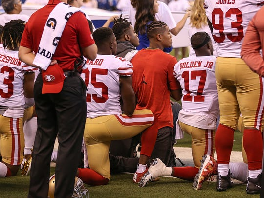 Some players from the San Francisco 49ers kneel during
