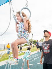 Douglas McClure, of 8 Fifty Sports & Fitness, right, watches as his daughter Kavya, 8, powers through a pull up at the new Fitness Court at Community Maritime Park on April 27. Pensacola Community Fitness Day will be held at the Fitness Court on Saturday.