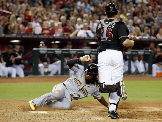 Pittsburgh Pirates' Andrew McCutchen, left, scores a run as Arizona Diamondbacks' Miguel Montero arrives late for a tag attempt during the eighth inning of a baseball game on Saturday, Aug. 2, 2014, in Phoenix. (AP Photo/Ross D. Franklin)
