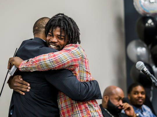 Marquan Richardson hugs peer support specialist Corie Priest after receiving his certificate of completion during the graduation ceremony for members of The Achievement Center on Thursday evening.