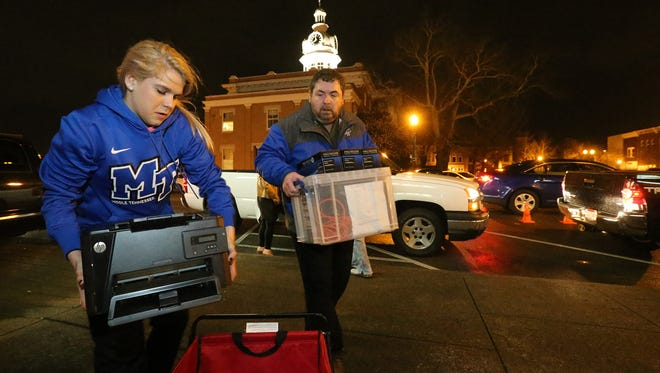MTSU womens basketball player Katie Collier, left and Eric Snyder help move ballots and other election items back to the Rutherford County Election Commission Office on Election Day March 1, 2016.