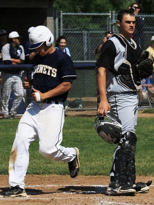 Looking on glumly as another Saline runner scores Saturday is Plymouth senior catcher Andrew Jossey.
