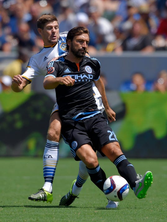 FILE - In this Aug. 23, 2015, file photo, Los Angeles Galaxy midfielder Steven Gerrard, left, of England, battles for the ball with New York City FC midfielder Andrea Pirlo, of Italy, during the first half of a MLS soccer match in Carson, Calif. Major League Soccer had a tremendous influx of superstar European players in 2015, but some adjusted to the league's heat, altitude and lengthy travel more quickly than others. LA's Steven Gerrard and NYCFC's Andrea Pirlo are among the big names planning on better seasons this summer. (AP Photo/Mark J. Terrill, File)
