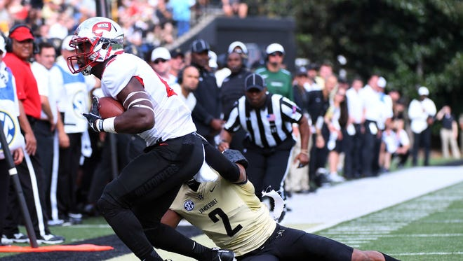 Western Kentucky tight end Mik'Quan Deane (85) catches a pass along the sideline as he is defended by Vanderbilt safety Arnold Tarpley III (2) on Saturday in Nashville, Tennessee.