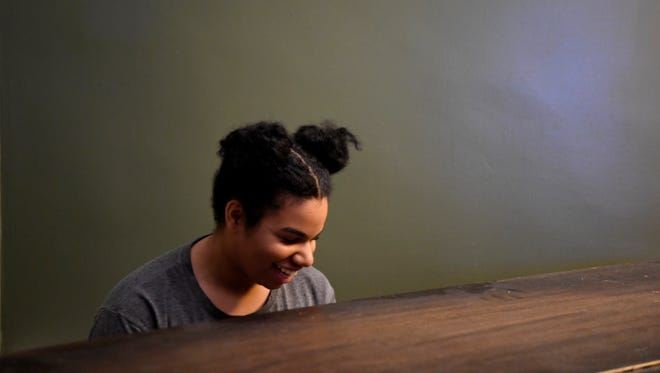 Wé McDonald playing the piano in her home in Paterson.