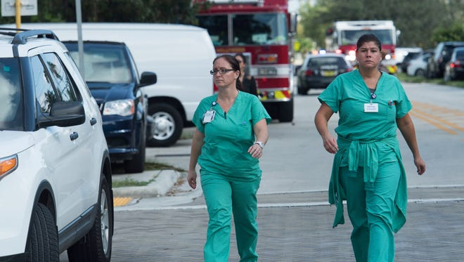 Healthcare workers walk down the street near Memorial Regional Hospital in Hollywood Fla.  after five residents at a Florida nursing home that lost power during Hurricane Irma  died after a loss of air conditioning during the outage, Broward County officials said Wednesday. Police Chief Tomas Sanchez said another 115 patients were evacuated, including several in critical condition. His office immediately started a criminal investigation, but Sanchez did not indicate specifically what the office was looking for. 