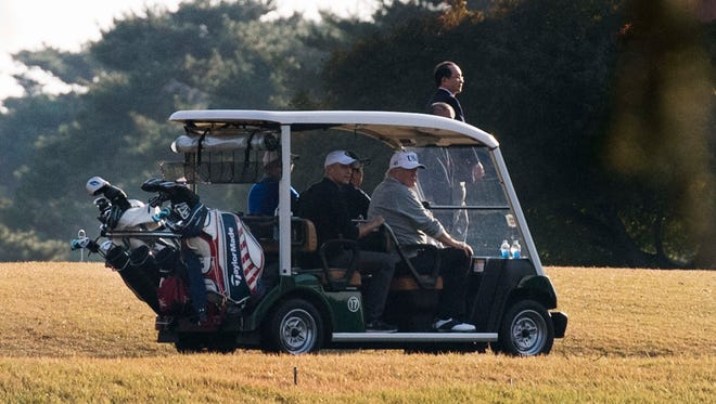 President Trump (front, right) and Japanese Prime Minister Shinzo Abe (front, left) return in a golf cart after playing a round of golf at the Kasumigaseki Country Club Golf Course in Kawagoe, Saitama prefecture, outside Tokyo on November 5, 2017.