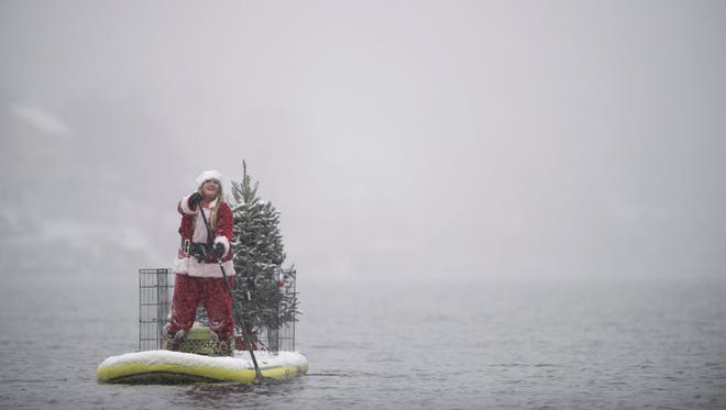 Micki Lees, owner of Jersey Paddle Boards, paddles toward the shore Saturday during the annual Santa Paddle Board Takeover at Greenwood Lake.