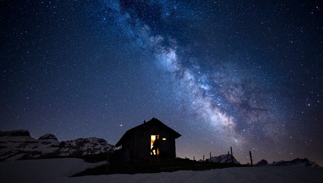 A man is silhouetted against the illuminated inside of a small cabin with a view of the 'Milky Way'  galaxy in the sky over the Ormont Valley, Switzerland.