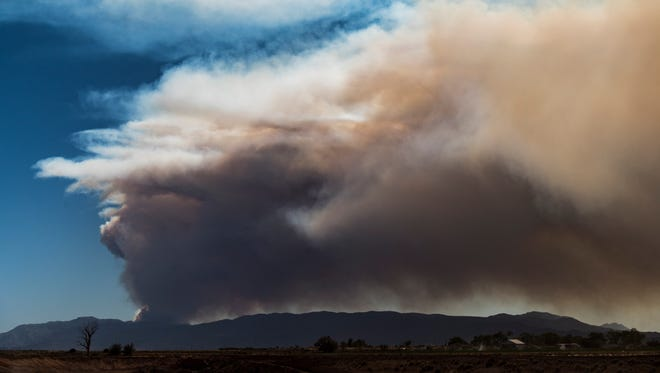 Smoke rises over the mountains from a wildfire near Pine Valley on Wednesday, June 27, 2018.