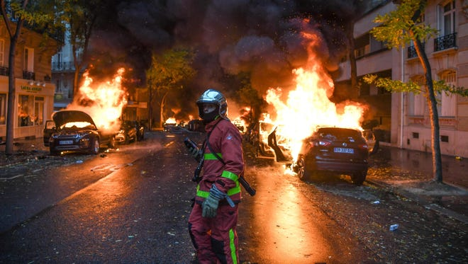A firefighter looks on as cars are burning during a protest of Yellow vests (Gilets jaunes) against rising oil prices and living costs, on December 1, 2018 in Paris. Speaking at the Paris police's command centre, French Prime Minister said 36,000 people were protesting across France, including 5,500 in the capital for this 3rd nationwide day of blockade ands demos.