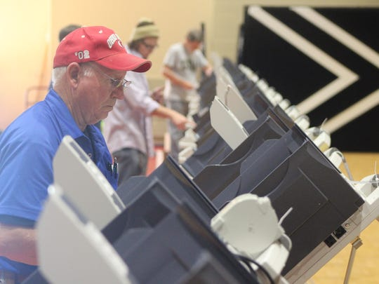 Norm Abraham and other volunteers set up voting machines