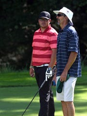 Sean Thomas, left, and his father, Scott, talk strategy prior to hitting his tee shot on the par-17th hole during the final round of the Zanesville District Golf Association Amateur tournament on Saturday at Zanesville Country Club. Thomas, a Newark Catholic grad who plays at Mount Vernon Nazarene, shot a 4-under-par 68 to earn a 13-shot win over Warsaw's Brad Baker and Granville's Drew Coen.