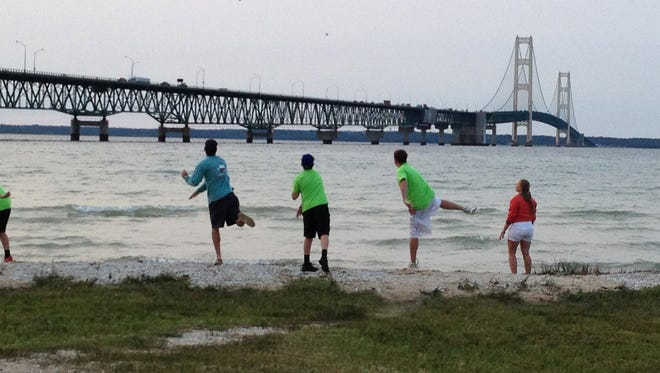 Boys all throw stones into Lake Huron all at once on a cool July night in Mackinac City, Mich. Thursday, July 26, 2014. Ellen Creager/Detroit Free Press