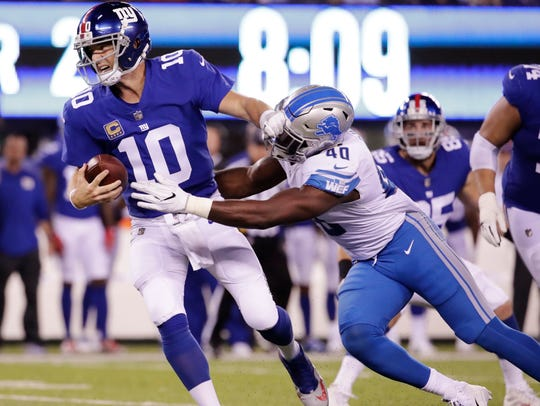 Giants quarterback Eli Manning is sacked by Lions linebacker