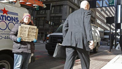 Tanya Smith of Taylor Mill holds her sign, looking for donations this week along Walnut Street in downtown Cincinnati.