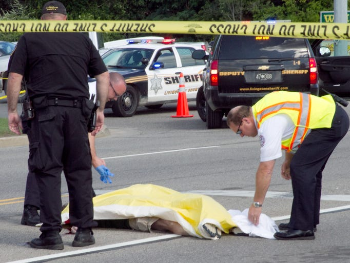 Sheriff and EMS personnel cover the body of a deceased subject laying in the middle of Grand River Avenue at Chilson Road in Genoa Twp. near Howell. The victim was later identified asDerek Flemming.