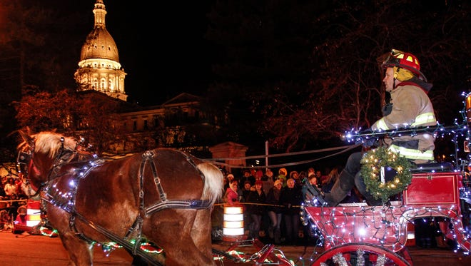 A Lansing Firefighter is pulled by two horses during the Electric Light Parade, Nov. 21, 2014, in downtown Lansing, during the 30th Annual Silver Bells in the City celebration.