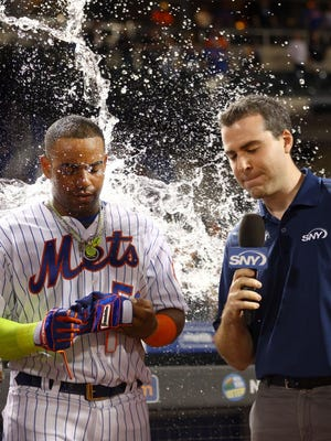 Mets left fielder Yoenis Cespedes is doused by Mets second baseman Wilmer Flores in front of reporter Steve Gelbs after hitting a walk-off home run against the Miami Marlins to give New York a 2-1 win in 10 innings Monday night at Citi Field.