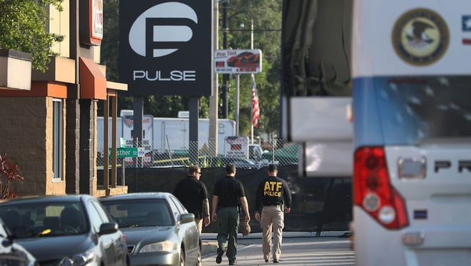 Law enforcement officials investigate the Pulse nightclub shooting in Orlando on June 15, 2017.