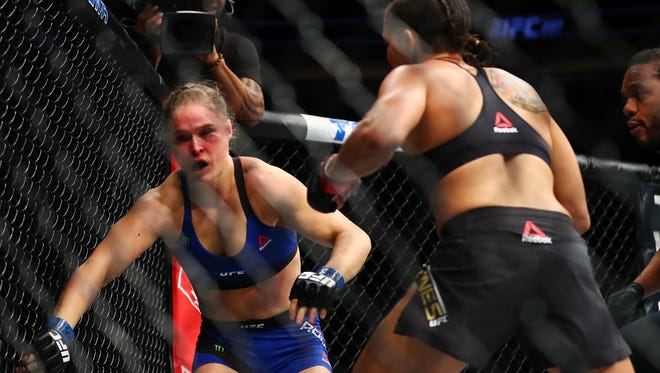 Ronda Rousey reacts to Amanda Nunes' attack during UFC 207.