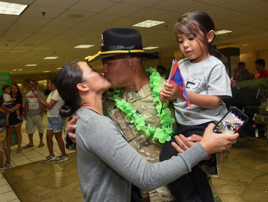 Sgt. Brandon Sana kisses his wife Barbara with their