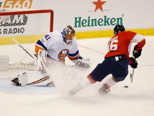 Florida Panthers center Aleksander Barkov (16) attempts a shot at New York Islanders goalie Jaroslav Halak (41) during the first period of an NHL hockey game, Monday, Dec. 4, 2017, in Sunrise, Fla. (AP Photo/Wilfredo Lee)