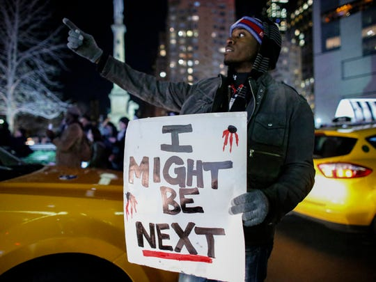 A man holds a sign as he takes part in a Dec. 3, 2014, protest on 6th Avenue in Manhattan after a grand jury decided not to indict New York Police Officer Daniel Pantaleo in Eric Garner's death.