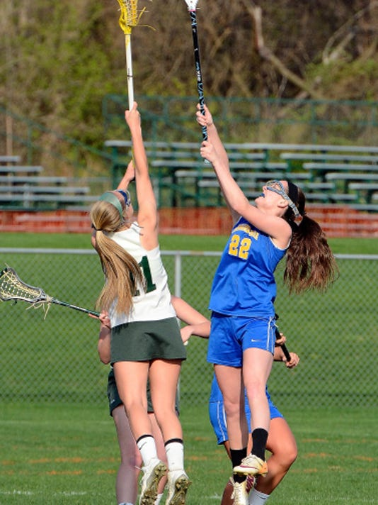 Kennard-Dale's Morgan Day, right, leaps for the ball on a faceoff recently against York Catholic's Lisa Casagrande. Day is now the all-time leading goal scorer in PIAA girls' lacrosse.