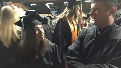 In this Wednesday, May 10, 2017 photo, Wor-Wic Community College candidates for graduation Caitlyn Causey of Salisbury and Christopher Hannon Dombrosky of Ocean City and Baltimore chat while waiting to march into the arena at the Wicomico Youth & Civic Center in Salisbury to receive associate of arts degrees in general studies. Dombrosky also was a candidate for an associate business degree.