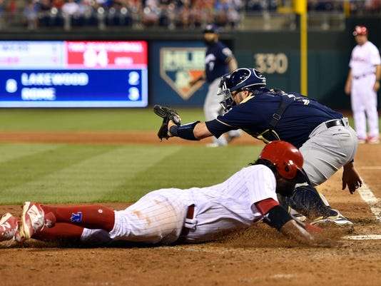 Philadelphia Phillies' Odubel Herrera slides safely to score past Milwaukee Brewers catcher Manny Pina during the sixth inning of a baseball game, Friday, July 21, 2017, in Philadelphia. (AP Photo/Derik Hamilton)