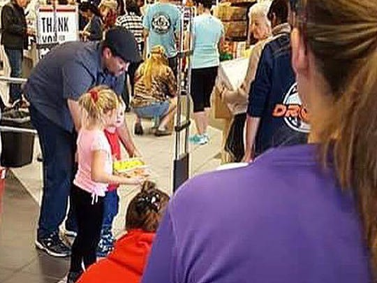 Kevin Johnston and his children, Clare and Connor, share cookies with people waiting in line at the post office.