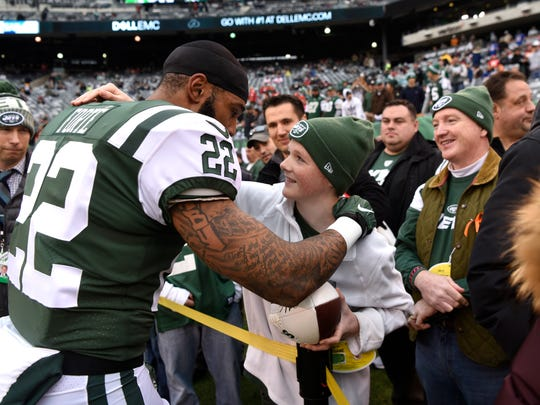 New York Jets running back Matt Forte (22) hugs Liam O'Brien of Garden City, N.Y., after signing his football. Kansas City Chiefs at the New York Jets in East Rutherford, NJ on Sunday, December 3, 2017.
