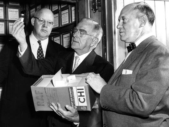 Dr. Herman N. Bundesen, center, holds up a container of the Salk vaccine to prevent Polio with Dr. Robert Mac Fate, left, and Dr. William Fishbein, on April 18, 1955, at the Board of Health. The three are shown with $140,000 worth of the vaccine.