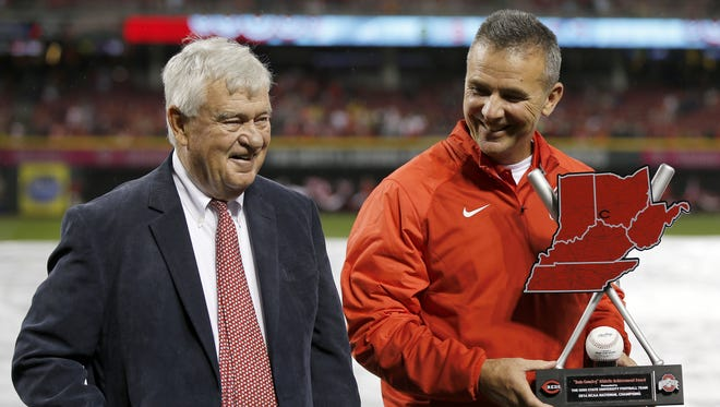 Reds President and CEO Bob Castellini, left, presents Ohio State football coach Urban Meyer with the first-ever Reds Country Athletic Achievement Award before the Opening Night game against the Pittsburgh Pirates.