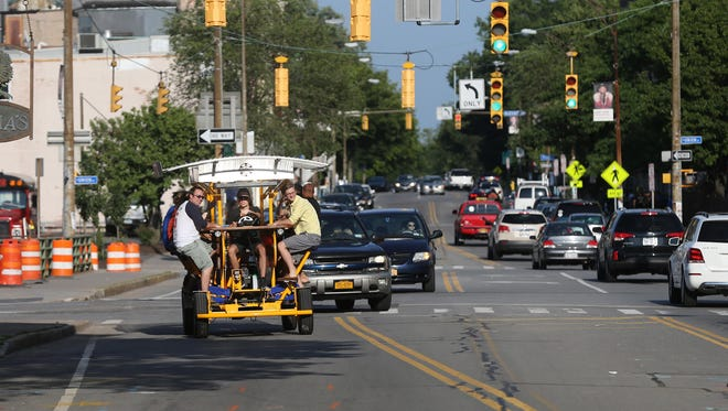 Riders on the Rochester Pedal Tours vehicle enjoy a bar-hopping ride through traffic along East Avenue on July 10, 2015.