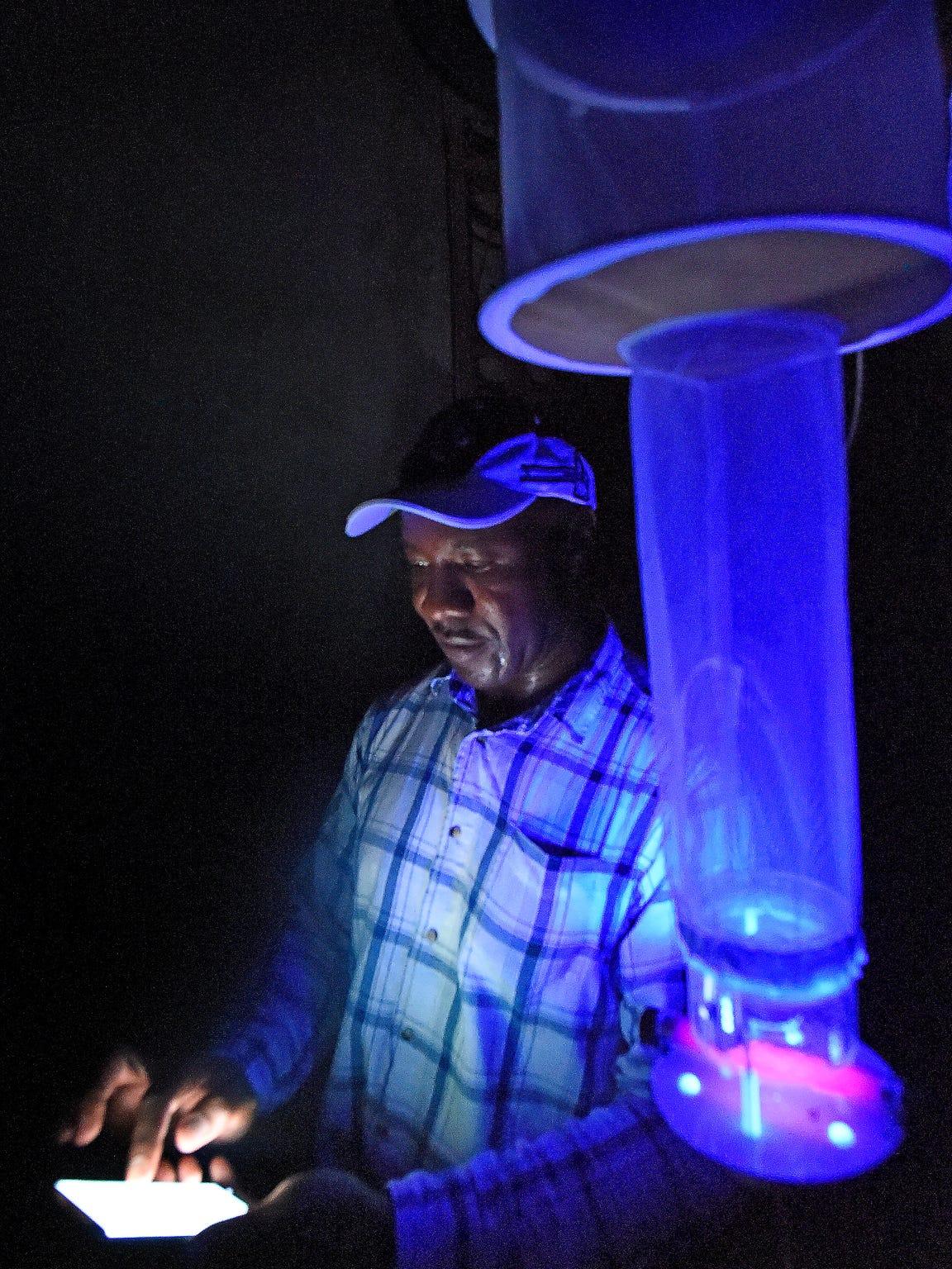 Dr. Bernard Okech checks his phone as he sets mosquito
