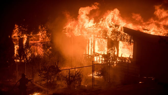 A firefighter sprays water as flames from a wildfire consume a residence near Oroville, Calif., on Sunday, July 9, 2017.