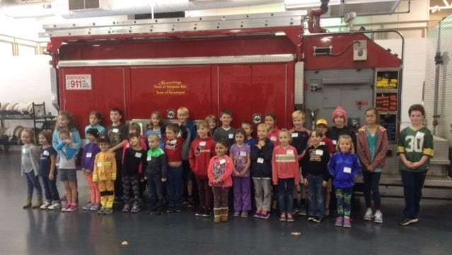 Some of the honorary firefighters gathered for a photo in the Sturgeon Bay fire station Saturday, Oct. 21, 2017.