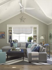 Shades of gray are used as a neutral base while bright, inviting shades of blue that evoke the ocean bring the space to life in a family room.
