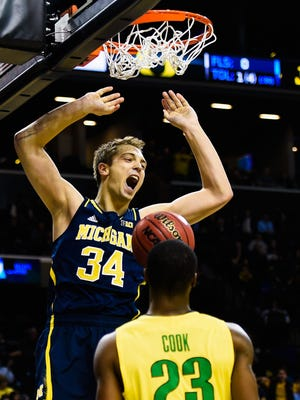 Mark Donnal #34 of the Michigan Wolverines reacts after a dunk in the first half during a game against the Oregon Ducks at the Barclays Center on November 24, 2014 in the Brooklyn borough of New York City.