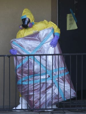 A hazardous material cleaner removes a wrapped item from the apartment where Thomas Eric Duncan, the Ebola patient who traveled from Liberia to Dallas, stayed.