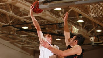 Muskingum freshman Marcus Dempsey goes up for a shot against a Heidelberg defender earlier this season. The Tri-Valley product has aided the Muskies' turnaround this season.